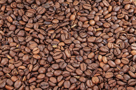 Mosaic made up of many coffee beans, which look light in color because the environment is very bright. It serves as a texture or background.