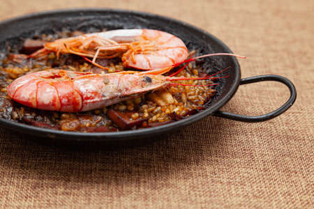 Detail shot of a recipe for rice, fish, seafood and squid ink cooked in a small paella on a sackcloth surface. There are two large prawns and it is ready to eat.