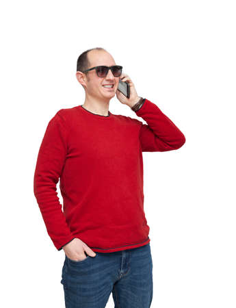 A bald young man in sunglasses is making a call with his mobile phone. The person is dressed in a red sweater, jeans, wears a watch and is smiling. The background is white. Foto de archivo