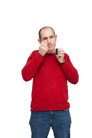 A bald young man wearing a red sweater is snacking on dairy with a metal spoon. He has the food in his mouth. The background is white.