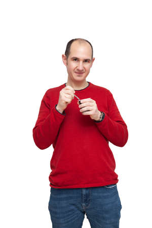A bald young man wearing a red sweater is snacking on dairy with a metal spoon. He has food in the cutlery. The background is white.