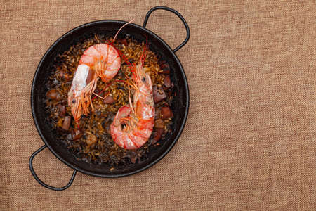 Recipe for rice, fish, seafood and squid ink cooked in a small paella on a sackcloth surface. There are two large prawns and it is ready to eat.