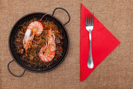 Recipe for rice, fish, seafood and squid ink cooked in a small paella on a sackcloth surface. There are two large prawns and it is ready to eat. There is a red napkin and a fork. Foto de archivo