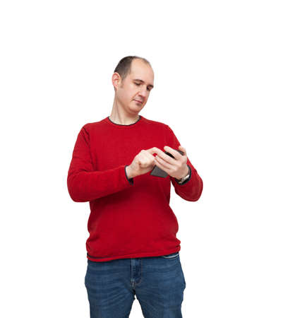A bald young man is typing a message with his mobile phone. The person is dressed in a red sweater, jeans and wears a watch. The background is white.