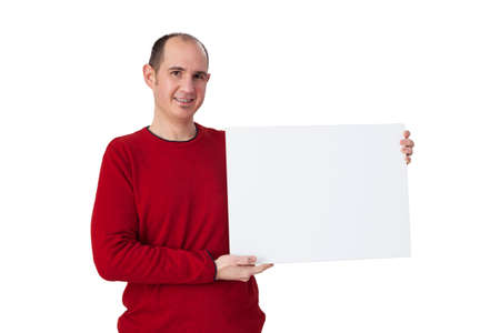 A bald young man holding a blank poster horizontally positioned to the right of the image. The adult person is wearing a red sweater. The background is white. Foto de archivo