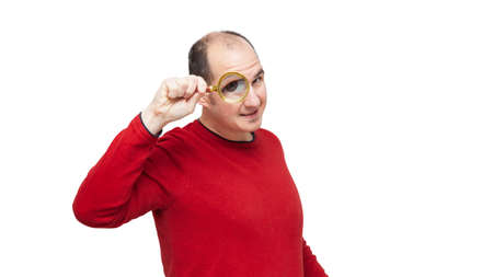 A bald young man wearing a red sweater is looking forward through a magnifying glass and his right eye is very large. The background is white.