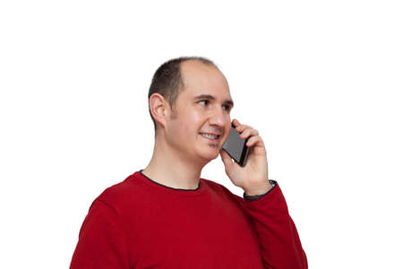 A bald young man dressed in a red sweater is holding his smartphone next to his ear with his left hand and is chatting with someone. The background is white.