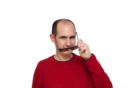 A bald young man dressed in a red sweater looking forward while with his left hand he is placing his dark glasses in front of his eyes. The background is white.