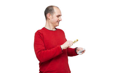 A bald young man in a red sweater is reading a medicine leaflet with a magnifying glass because the print is too small. The background is white. Foto de archivo