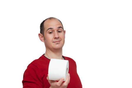 A bald young man dressed in a red jumper taking in his right hand a roll of toilet paper and looking at it with a funny expression. The background is white.