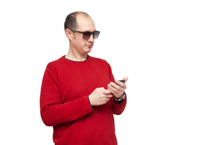 A bald young man dressed in a red sweater and sunglasses is reading and typing messages with his smartphone typing with his touch screen. The background is white.