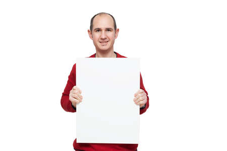 A bald young man dressed in a red sweater is holding with his hands a blank poster in front of himself placed vertically. The background is white.