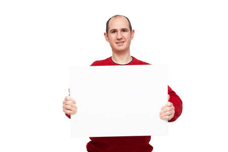 A bald young man dressed in a red sweater is holding with his hands a blank poster in front of himself placed horizontally. The background is white.