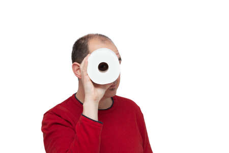A bald young man in a red sweater peering through the toilet paper tube like a spyglass. The background is white.