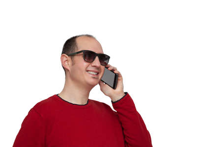 A bald young man dressed in a red sweater and sunglasses is holding his smartphone with his left hand next to his ear and is chatting with someone. The background is white. Foto de archivo