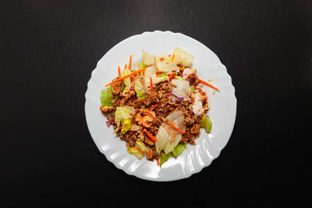 Salad recipe with brown rice, carrots, lettuce, crunchy onion, walnuts, sunflower and pumpkin seeds, ham, olive oil and salt. The ingredients are mixed in a porcelain plate on a black bench.