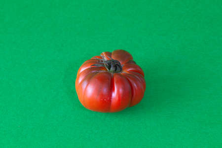 Red tomato of the raft variety isolated on a green background. The vegetable has small green leaves, wrinkles and cracks.