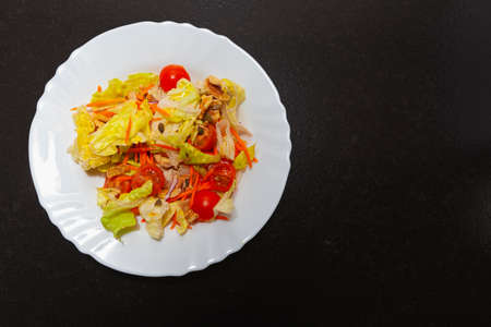 Combination of vegetables and greens in a ceramic plate on a dark bench in a kitchen. The recipe calls for lettuce, cherry tomato, carrot, walnuts, onion, seeds, aromatic herbs, olive oil and salt.