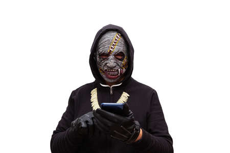 A man disguised in a zombie mask wearing a black hooded sweatshirt is touching the touch screen of a cell phone.