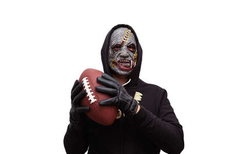 A man disguised in a zombie mask wearing a black hooded sweatshirt is holding a football ball in his hands.