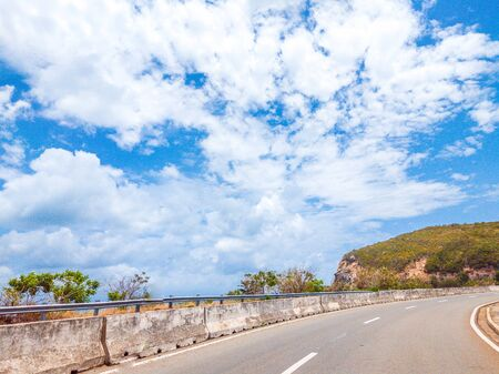 Dry asphalt empty automobile curved road with concrete barrier and marking lines in mountains on a sunny summer day with blue cloudy sky. Car travel trip concept background.