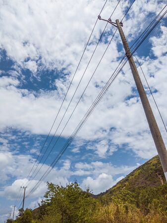 Electric pole with wires cables on blue cloudy sky and green mountains background. Stories vertical format.