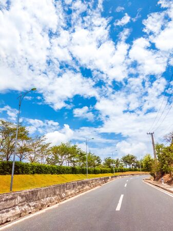 Dry asphalt empty automobile road with concrete barrier and marking lines on a sunny summer day with blue cloudy sky. Car travel trip concept background. Stories vertical format.