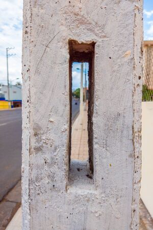 A Hole in a concrete wall with city view.