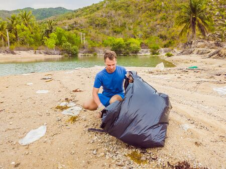 Man in gloves pick up plastic bags that pollute sea. Problem of spilled rubbish trash garbage on the beach sand caused by man-made pollution and environmental, campaign to clean volunteer in concept