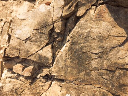 Natural background. Closeup edged shabby cliff cracks. Gray-brown stone rock texture of mountains. Vintage and faded matt style colour in tinted photo. Concept of geolog, mountaineering or hard work.