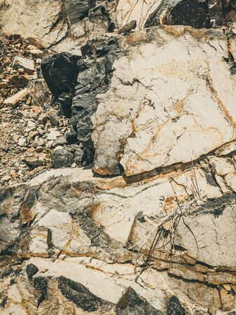 Natural background. Closeup edged shabby cliff cracks. Gray-brown stone rock texture of mountains. Vintage and faded matt style colour in tinted photo. Concept of geolog, mountaineering or hard work