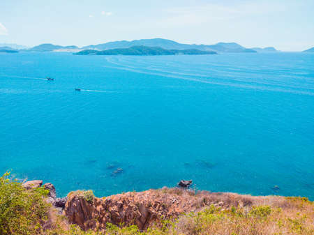Deep blue ocean panorama with boat in a turquoise tropical sea under clear sky background. Tropical holiday paradise concept, the end of quarantine Covid 19 isolation - beginning of normal life again
