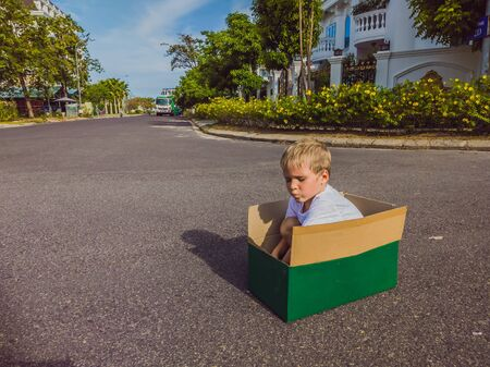Cute little child boy sitting inside cardboard box on silent street in modern comfortable cottage village. Childhood and moving out concept