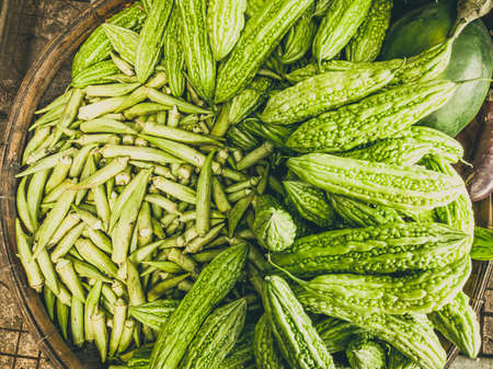Closeup heap of momordica and okra in braided basket. Harvested young fresh organic bio antiparasitic, anthelmintic raw veggies on the market. Cooking, healthy food, vitamins for strong immunity