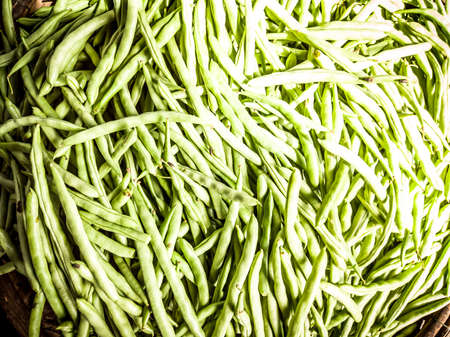 Close-up heap of pile raw green beans on a local asia farmers market. Cooking and healthy food concept, vitamins for strong immunity, good nutritional value