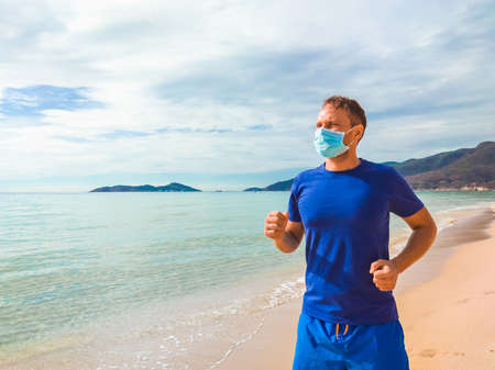 Coronavirus COVID 19. Young beautiful man doing sport performing workouts exercises and running near sea in the morning during quarantine. Active life in surgical sterilizing face mask protection Stok Fotoğraf