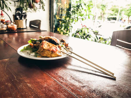 Have a break. Vegetarian food can be delicious for everybody. Fried soy meat with rice and stew vegetables in white plate with chopsticks in simple asian vegan cafe. Healthy eating, caring for animals