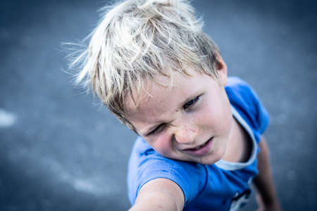 Portrait of a funny happy mischievous cheerful cute blond blue eyed boy making freckles dirty face while playing, laughing. Nursery, happy childhood, education, family relationship concept