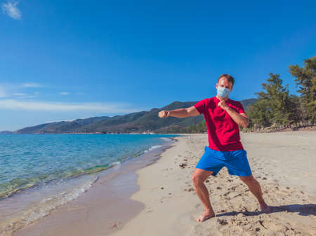 Young muscle man in medical mask perform outdoor workouts in the park near sea during second wave coronavirus Covid 19 pandemic quarantine. Kick training pose, swing arms and legs, sport active life Banque d'images