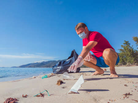Activist volunteer Man in medical face mask pick up garbage that pollute beach sand near sea. Problem of spilled rubbish trash caused by man-made, planet pollution and environmental protection concept Stock fotó