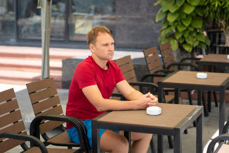 Serious blond man in casual style red t-shirt sit in modern cafe, nervous waiting someone or changes, thinking. Skin small photoshop. Human relationship, difficulties during covid or life problems