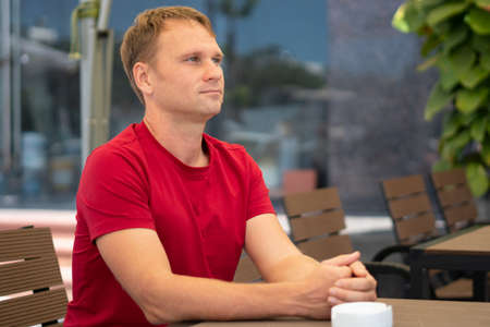 Half side portrait restrained smile handsome young blond man in casual red t-shirt sit in modern cafe, happy look away, waiting someone or met already. Human relationship, good future changes concept