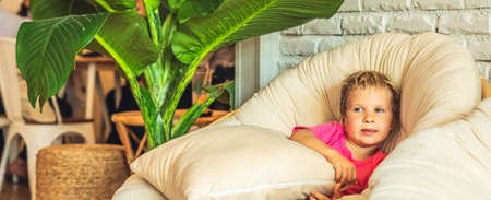 Blond scared boy in pink tshirt tucked knees sit under pillow in a round fashionable chair in living room in a house indoor. Family relationship, childhood problems behaviour, education psychology