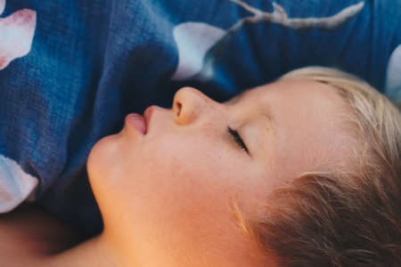 Cute little boy sleep sweetly on pillow with bright morning sunbeams from window, taking a nap. Happy bedtime for kids. Problem of early awakening, late falling asleep, health sleep biorhythms