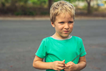 Funny mischievous cute blond boy with freckled face restrained smile, artistic emotions. Behaviour education problems psychology, family relationship, simple joys of happy childhood, people concept