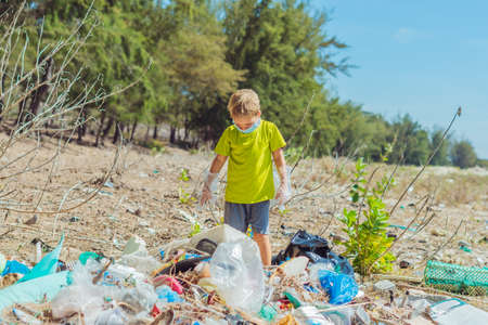 Volunteer boy in face mask helps to pick up garbage which pollute beach near forest. Problem of spilled rubbish trash planet pollution environmental protection concept. Natural children education