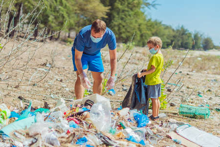 Volunteers in blue face mask. Father, son pick up garbage which pollute beach near lazur sea. Problem of spilled rubbish trash planet pollution environmental protection. Natural children education