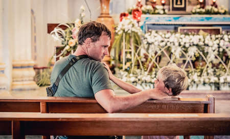 Christian dad tells his son Bible stories about Jesus sitting in kirk. Faith, religious education, modern church, father day, fatherly responsibilities, father influence on formation of son worldview Stock Photo