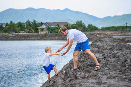 Dad helps son go down to lake water, explains safety rules. Family together walk play. Home natural child education, fathers day, fatherly responsibilities, influence on formation of son worldview