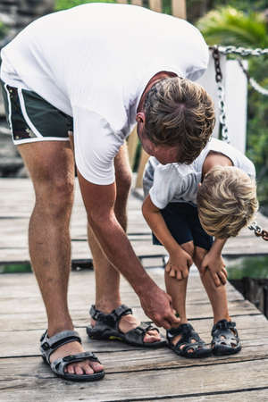 Little boy scraped looking leg, father disinfects the wound provides medical assistance first aid while walk in the park or smears insect bites with antiallergic liquid Stock Photo
